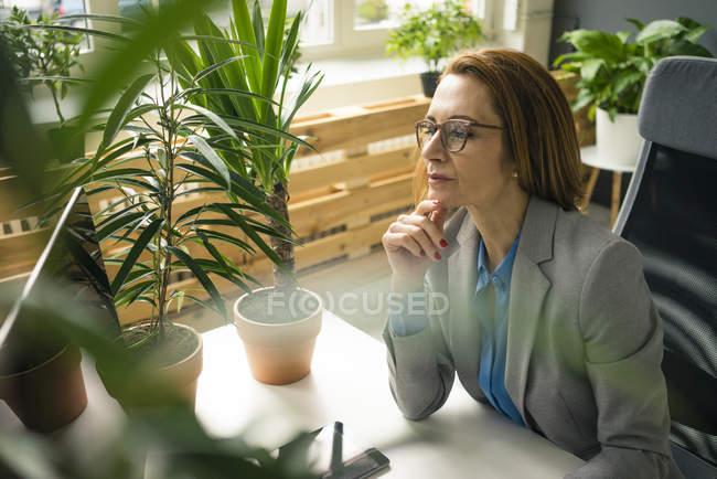 Зрелая деловая женщина, работающая в устойчивом офисе, с растениями на столе — стоковое фото