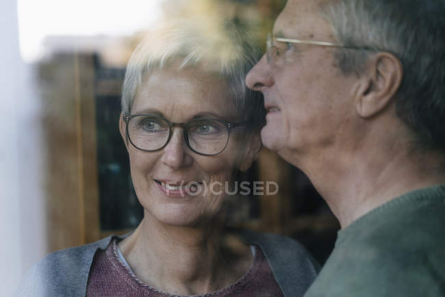 Casal sênior confiante olhando pela janela — Fotografia de Stock