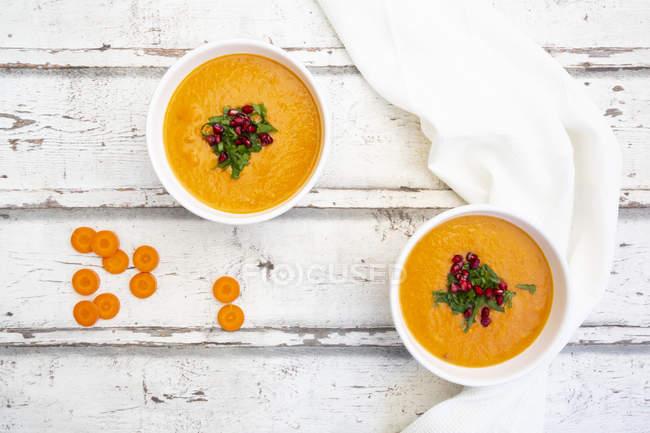 Bacia de sopa do coco do gengibre da cenoura com cobertura da semente da salsa e da romã — Fotografia de Stock