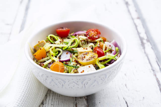Bowl of zoodles with fried tofu, red quinoa, red onions and tomatoes — Stock Photo