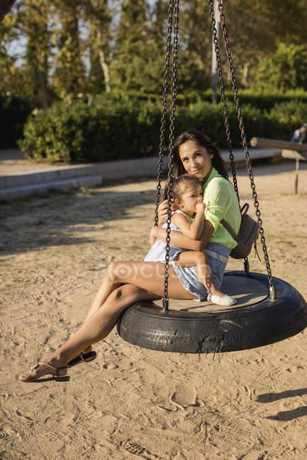Mère souriante avec sa fille assise sur une balançoire sur une aire de jeux — Photo de stock