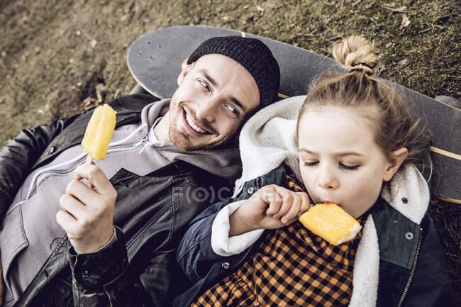 Батько з донькою відпочивають на скейті і їдять морозиво. — стокове фото