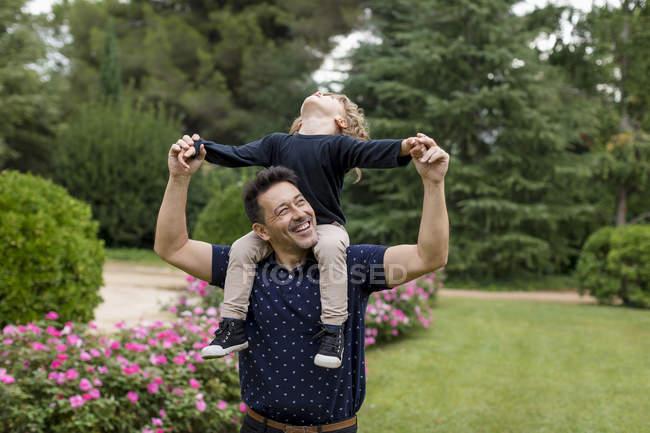 Buon padre che porta il figlio su spalle in parco — Foto stock
