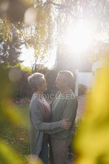 Cariñosa pareja de ancianos abrazándose en el jardín - foto de stock