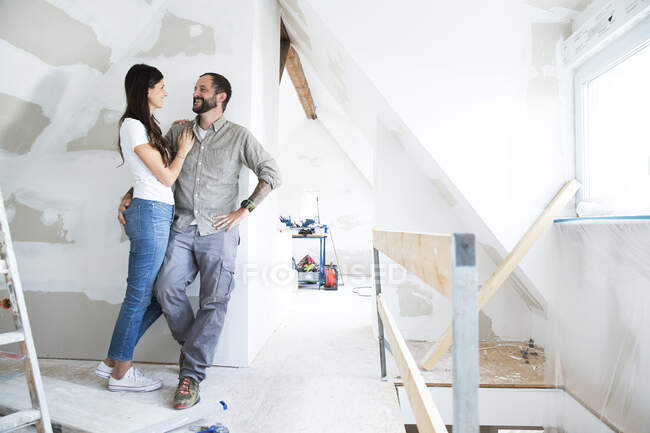 Smiling couple standing in attic to be renovated — Stock Photo