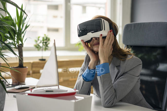 Businesswoman sitting at desk with a ship model, looking through VR glasses — Stock Photo