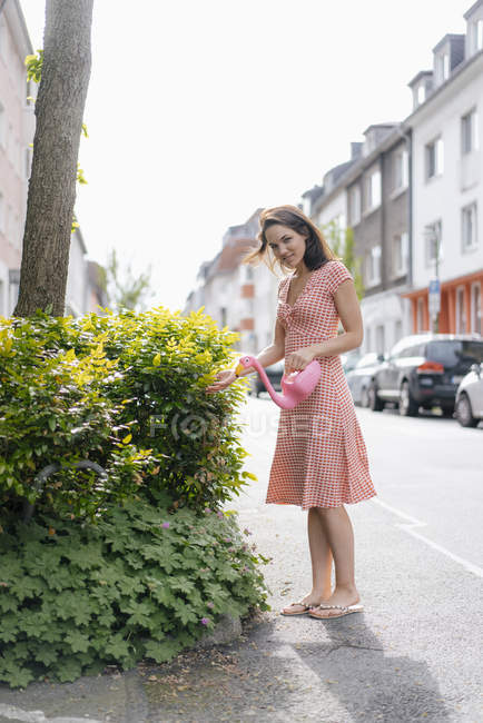 Woman watering plants with a flamingo can in an urban street — Stockfoto