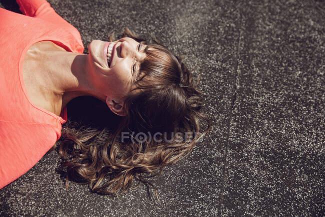 Обережна жінка сидить на даху, лежачи на даху. — стокове фото
