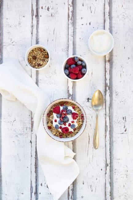 Schüssel Müsli mit griechischem Joghurt, Quinoa, Himbeeren, Blaubeeren und Granatapfelkernen — Stockfoto