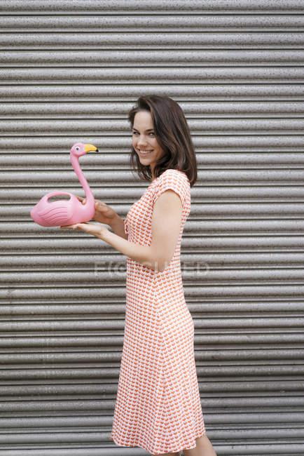 Mulher em vestido de verão com padrão de coração, segurando figura flamingo rosa — Fotografia de Stock