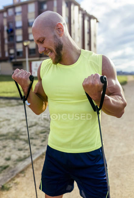 Muscular man exercising with expander outdoors — Stock Photo