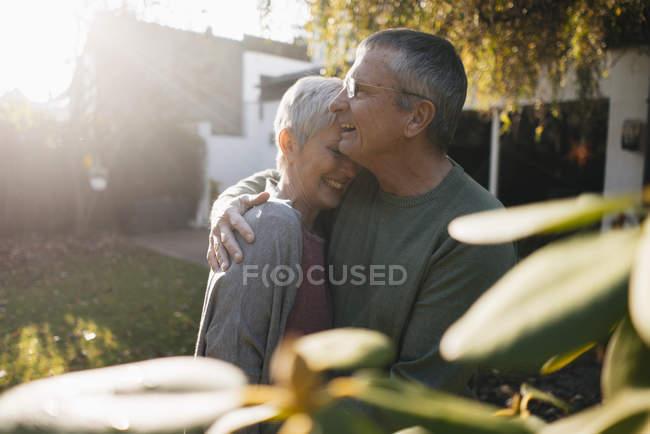 Счастливая любящая старшая пара обнимается в саду — стоковое фото
