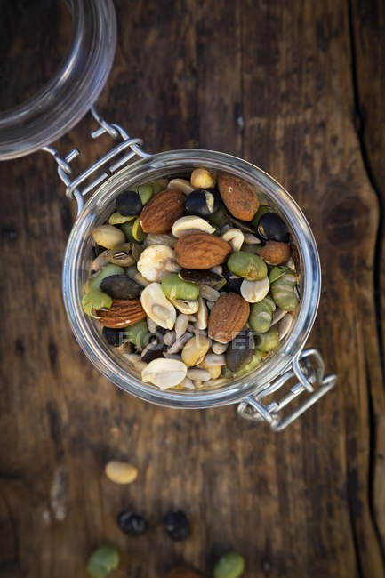 Preserving jar of roasted soy beans, seeds and nuts on wood — Stock Photo