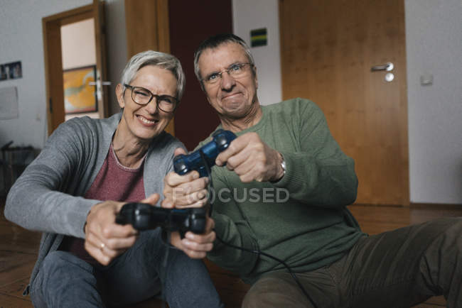 Happy senior couple playing video game at home — Stock Photo