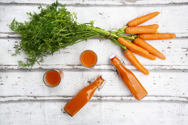 Carrots, glasses of carrot juice and swing top bottles on wood, from above — Photo de stock