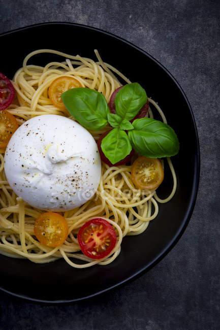Спагетті з помідорами, бурата і базиліком листя, зверху — стокове фото