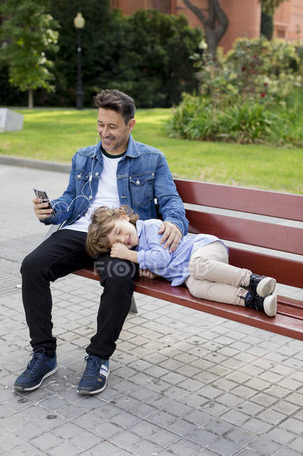 Happy father with son on a bench using cell phone and earbuds — Stock Photo