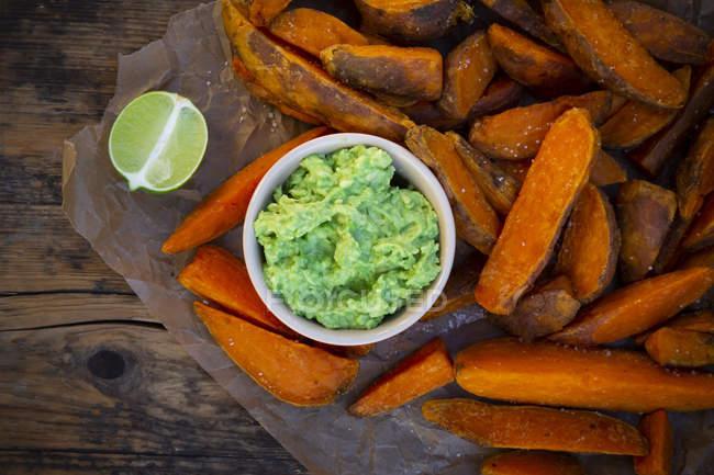 Сладкие картофельные клинья с соусом из авокадо — стоковое фото