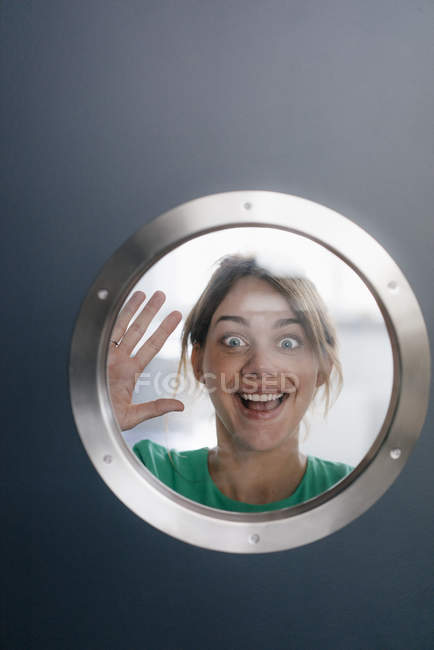 Retrato de mulher puxando caras engraçadas atrás porthole — Fotografia de Stock