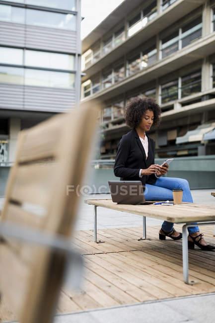 Бизнесмен с ноутбуком и кофе, чтобы пойти сидеть на террасе, глядя на смартфон — стоковое фото