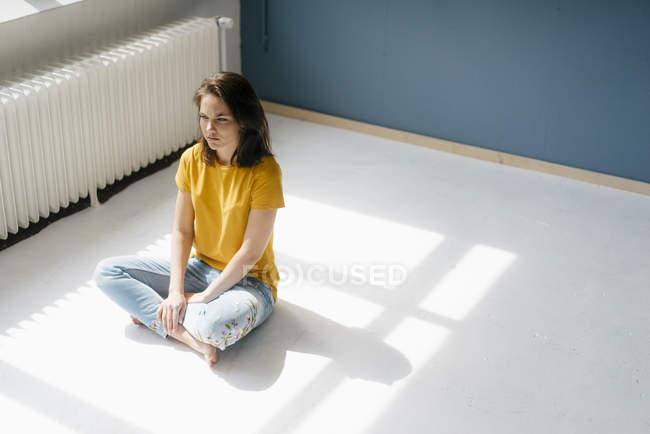 Pensive woman sitting in sunlight cross-legged on floor — Stockfoto