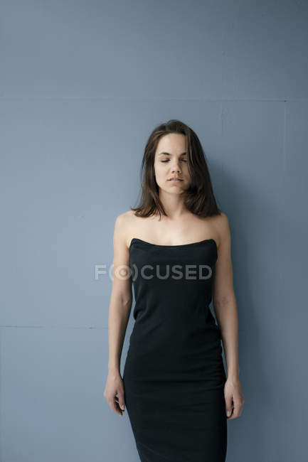 Pretty woman wearing dress, standing in front of blue background — Stock Photo