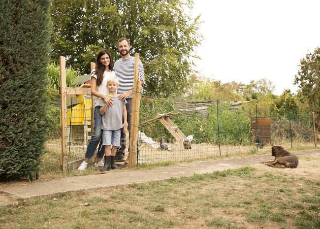 Портрет уверенной в себе семьи, стоящей у курятника в саду — стоковое фото