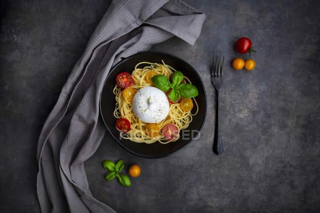 Espaguetis con tomates, burrata y hojas de albahaca, desde arriba - foto de stock