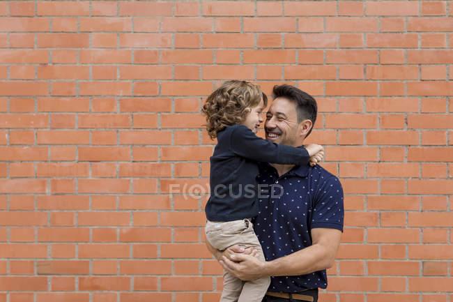Щасливий батько носив сина біля цегляної стіни. — стокове фото