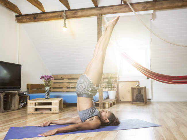 Young woman practicing yoga in attic — Stock Photo