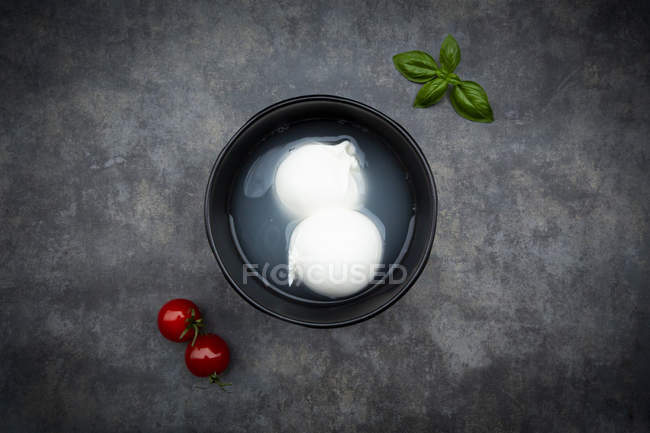 Tomatoes, basil leaves and burrata in bowl, from above — Stock Photo