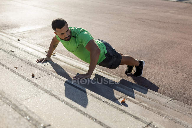 Sportive man during workout, pushup on step — Stock Photo