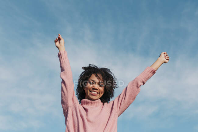Portrait of smiling young woman against sky raising hands — Stock Photo