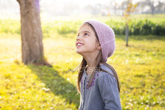 Portrait of smiling girl standing on a meadow in autumn looking up — Stock Photo