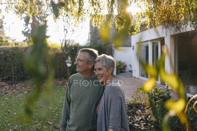 Feliz pareja mayor en el jardín mirando alrededor - foto de stock