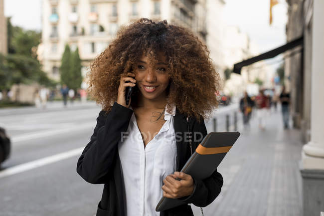 Young woman using smartphone, laptop bag — Stock Photo