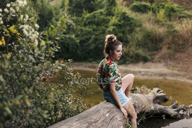 Young woman sitting on a trunk surrounded by nature — Stock Photo