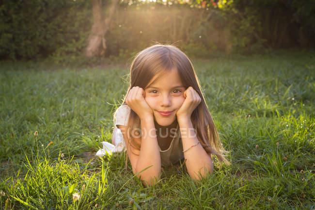 Portrait de petite fille allongée sur une prairie au crépuscule du soir — Photo de stock