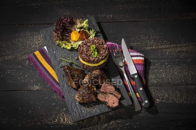 Bife canguru com arroz vermelho e manga em prato de ardósia — Fotografia de Stock