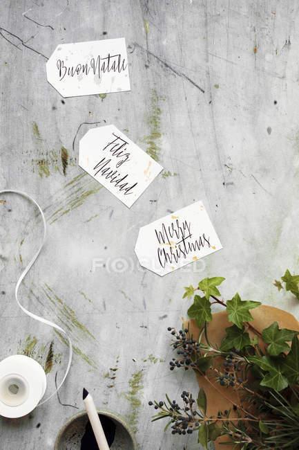 Frohe Weihnachten geschrieben in 3 verschiedenen Sprachen (Englisch, Italienisch, Spanisch) auf Kalligraphie Geschenkanhänger — Stockfoto