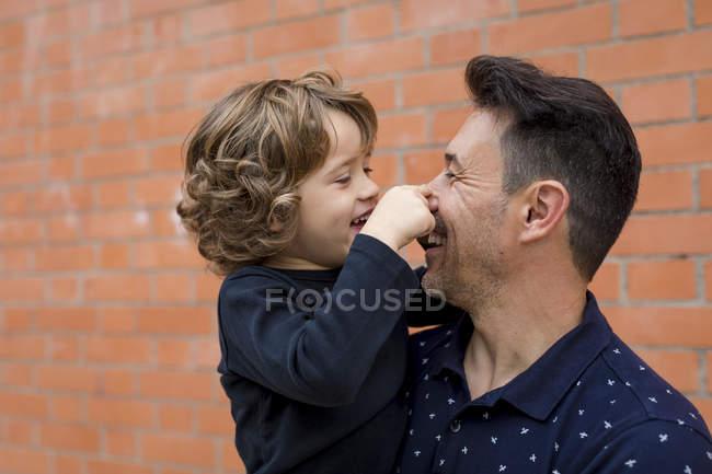 Père et fils ludiques au mur de briques — Photo de stock