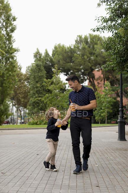 Щасливий батько і син йдуть з рукою з безалкогольними напоями. — стокове фото