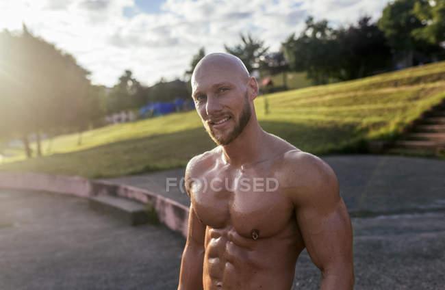 Портрет улыбающегося голого мускулистого человека на улице — стоковое фото