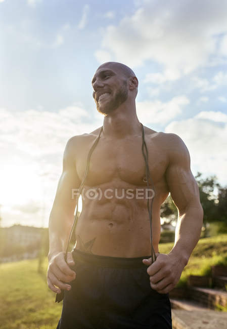 Portrait of smiling barechested muscular man with skipping rope outdoors — Stock Photo