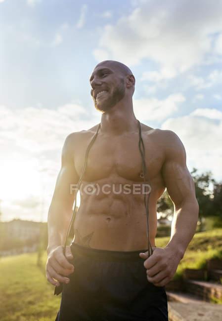 Retrato de sorrir homem musculoso barechested com pular corda ao ar livre — Fotografia de Stock