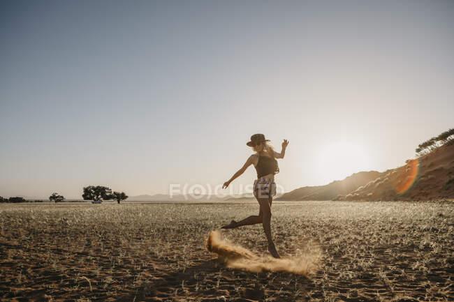 Namibia, el desierto de Namib, el Parque Nacional Namib-Naukluft, Sossusvlei, mujer en movimiento al atardecer en Elim Dune. - foto de stock