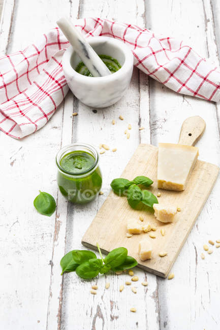 Vaso de pesto genovesa casero, ingredientes, mortero y toalla de cocina - foto de stock