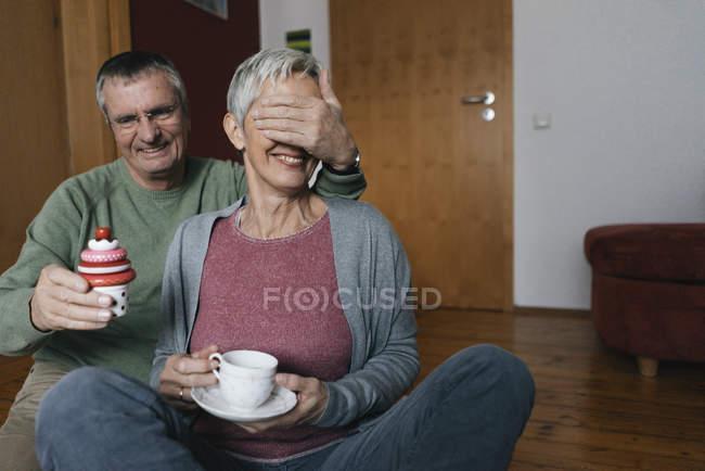 Feliz pareja mayor sentada en el piso en casa divirtiéndose - foto de stock
