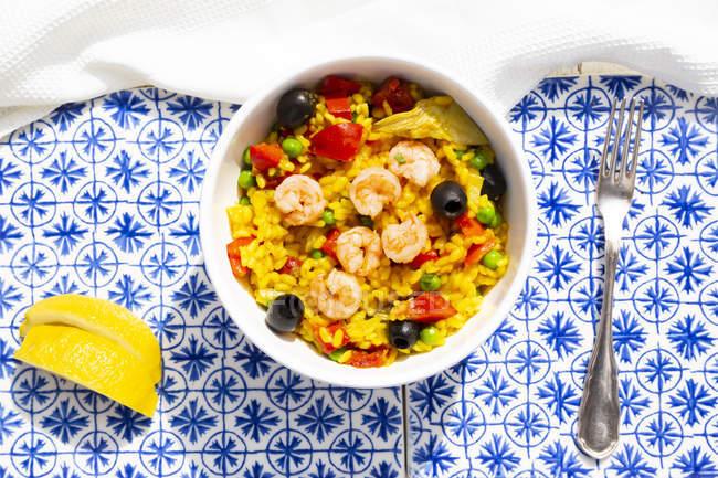 Paella com arroz, pimentão, tomate, alcachofra, ervilha, azeitona preta, curcuma e camarões — Fotografia de Stock