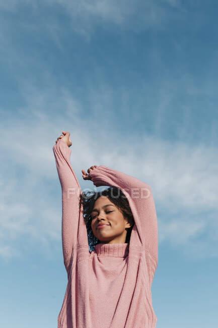 Retrato de sorrir jovem usando pulôver rosa contra o céu — Fotografia de Stock